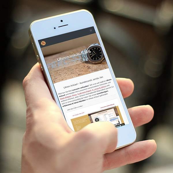 Eine Person hält ein Handy in der Hand, auf dem die Uhrenankauf365-Webseite angezeigt wird