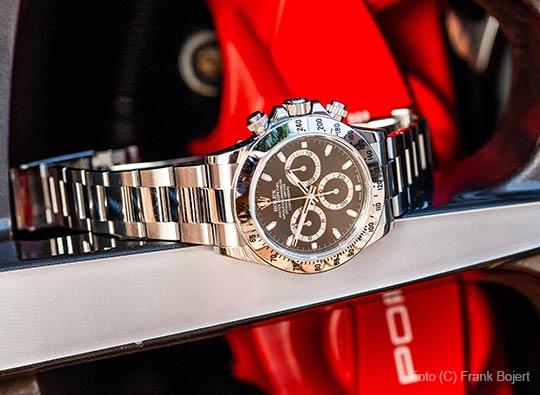 Rolex-Uhr auf einer Porsche-Felge liegend
